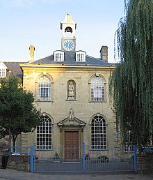 Yellow stone building with central 2 storey block with arched windows, hipped roof and clock tower