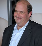 A smiling, heavyset, balding man wears a suit jacket and blue shirt.
