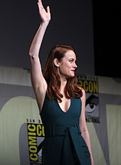 Brie Larson is seen waving, facing right