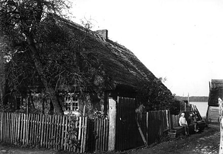 East Prussia, 1931: Ethnic Masurian children and Masurian farmhouse near a lake Bundesarchiv B 145 Bild-P017317, Ostpreussen, Masurisches Bauernhaus.jpg