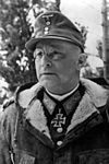 A black-and-white photograph of a man with glasses wearing a military uniform underneath a fur collared coat, field cap and neck order in shape of an Iron Cross.