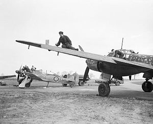 A photograph of a single–engined and a larger, twin engined aircraft on the ground. Two men are working on the wing of the larger aircraft. The engine–covers have been removed from the smaller aircraft and four men are working on its engine