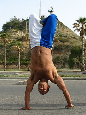 Handstand - A capoeirista performs a handstand with bent legs