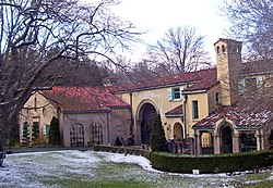 A gold-colored building with a red tiled roof and arches, pavilions and towers. There is an intermittent snow cover on the lawn in front, and two bare trees.