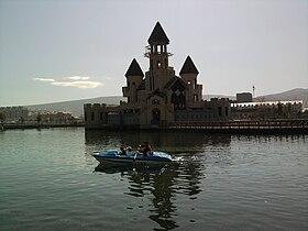 Замок в парке, стоящий на искусственном озере