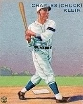A baseball-card image of a man wearing a white baseball uniform and cap and swinging a baseball bat