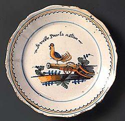 Dans le creux de l'assiette, un coq perché sur le fut d'un canon; la légende dit: je veille pour la nation