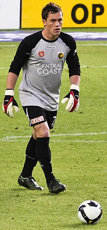A man with dark hair, wearing a grey shirt, black shorts and goalkeeping gloves approaching a football