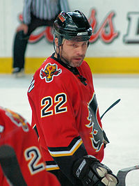 Hockey player in red uniform. He has turned his face toward the camera.