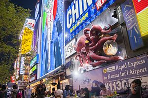 Dōtonbori - Visitors enjoy illuminated billboards, video screens and mechanized signs along the boardwalk