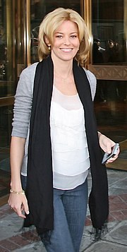 Elizabeth Banks, a blond caucasian woman in her early 30s, wears a grey open sweater with the sleeve up. She can be seen wearing a white blouse under and a black scarf around her neck, and wears a pair of blue jeans. In her left hand, she holds a grey cellphone. On her right hand, she wears a gold bracelet.