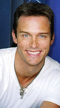 A man with dark hair wearing a white T-shirt including a silver necklace.