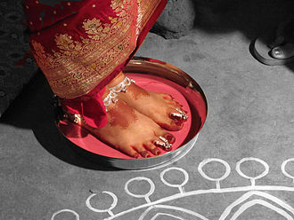 Bengali Hindu wedding - A ceremony welcoming the newly wed bride to her new home, with the feet dipped in a mixture of milk and alta.