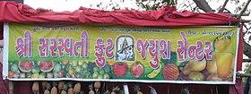 "śrī sarasvatī fruṭ jyuś senṭar - Shri Saraswati Fruit Juice Center. Note that ""Fruit Juice Center"" are English words. A Sanskritic alternative would be phaḷ ras kendra, or phaḷnā rasno kendra. It (kendra in particular) would however sound quite pedantic and out of place."