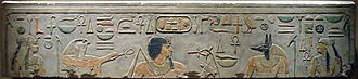 Light gray stone surface with carved and painted images of two woman, a falcon-headed god, a black-haired man with a long goatee, a jackal-headed god, and Egyptian hieroglyphs inscribed along the top