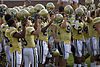 Football players wearing gold jerseys and white pants are standing closely to each other each holding their gold helmets in the air.
