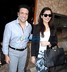 A smiling Govinda and his daughter, wearing sunglasses