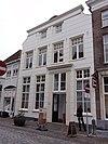 foto van Huis met schilddak en gebosseerd gepleisterde lijstgevel met ingezwenkte bovenhoeken, eenvoudige deuromlijsting. Nog geheel woonhuis