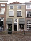 foto van Huis met schilddak en gebosseerd grijsgepleisterde lijstgevel, met winkel