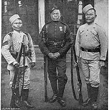 Three men in 1800s-style military uniforms stand holding rifles.