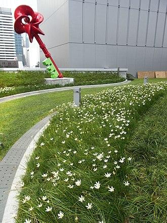 Tamar Park - Image: HK Admiralty Tamar Park red sculpture Key in art white flowers green plant Sept 2012