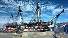 A picture of HMS Victory, the world's oldest commissioned naval ship, situated in Portsmouth's dry dock. The ship itself is missing its figurehead in this photo but retains its original sails.