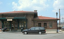 "Entrance to a train station, signs read ""Hastings-on-Hudson"", ""Station Cafe"", ""MTA Metro-North Railroad"". Two people are sitting out front drinking coffee, and a black Mercedes wagon is parked."