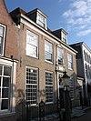 foto van Huis onder twee dwarse, achter elkaar liggende schilddaken en met lijstgevel. Versierde ingangstravee in ietwat verbasterde Lodewijk XV stijl, zoals ook het snijraam in het bovenlicht van de ingang