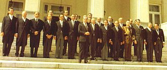 Amir-Abbas Hoveyda - 1975 cabinet - Shah of Iran Mohammad Reza Pahlavi is situated in the middle, with Amir Abbas Hoveyda to his left, and Jamshid Amouzegar on his right.