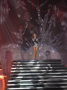 A brunette woman is singing. She is wearing a black dress. In front of her white stairs are seen.