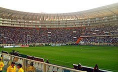 Photograph of a modern football stadium's interior; the stands are full of spectators