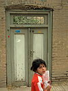 Iranian Nishapuri Elementary schoolgirl with texbook going to her classmate house for study together at evening - Aliov st - Nishapur.jpg