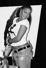 A sideshot of an African-American woman wearing jeans and a T-shirt. She smiles and stares behind herself, down towards the floor.