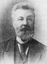 Old grainy photograph of the head and shoulders of a bearded man wearing a three-piece suit, tie and high collar