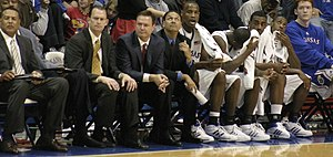 Bill Self - Self (third from left) sitting on the bench with his staff and players in a November 2007 game.