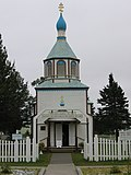 Photograph of the front of the Holy Assumption Orthodox Church, behind a white picket fence with white clapboard and a blue roof and onion dome.