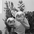 Kerstmis nadert jonge vrouw toont grote kerstballen, Bestanddeelnr 918-5560.jpg