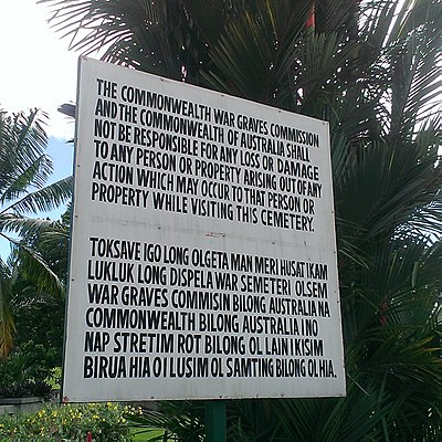 Lae War Cemetery TokPisin sign at front gate.jpg