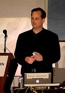 劳伦斯·雷席格站在有麦克风、上面放着一台笔电的讲台前。