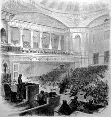 An etching of an ornate two story room filled with people seated in chairs on both the floor and balcony. At upper right is a dark fish shape.