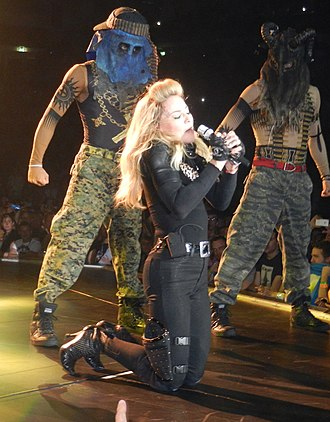 """True Blue (Madonna album) - Madonna performing """"Papa Don't Preach"""" on The MDNA Tour of 2012. It became Madonna's fourth number-one single on the Billboard Hot 100 chart."""