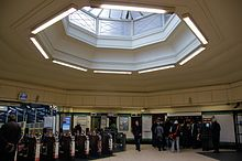 A station ticket hall with automatic ticket gates on the left and passengers waiting to buy tickets from a machine in the wall. A large octagonal roof light occupies the central portion of the ceiling with a deep convex moulding around the opening.