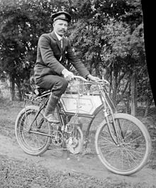Man wearing cap & suit on motorised pushbike, Mt Buffalo Vic, Alice Manfield.jpg