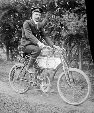 Motorized bicycle - A man on a Minerva motorized bicycle in Australia not long after the start of the 20th century (photo by Alice Manfield); a small internal combustion engine drives a belt attached to the rear wheel