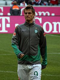 A photograph of a blonde man wearing a grey and green training jacket and white shorts, the man is seen on a football pitch in the process of warming up.