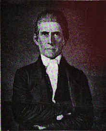 A man with slicked-back, dark hair wearing a white shirt and dark jacket