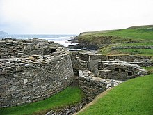 Un mur de pierre semi-circulaire à gauche suggère l'existence d'un grand et ancien bâtiment et à droite les ruines de diverses autres structures en pierre.  À l'arrière-plan, une falaise basse sépare un plan d'eau des champs herbeux.