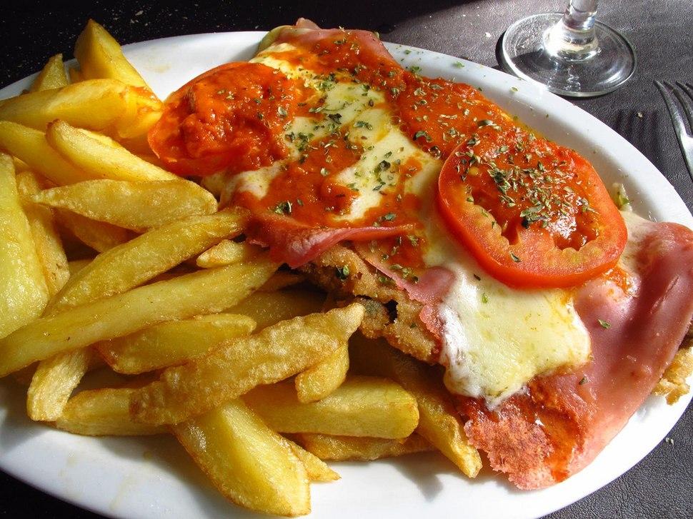 Milanesa napolitana con papas fritas rodajas de tomate y orégano