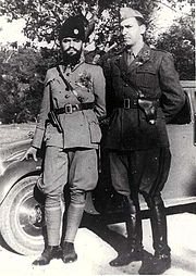 two males in uniform leaning against a car