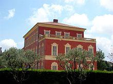 Vue d'un bâtiment en rouge avec façade en trompe-l'œil sous un ciel bleu avec deux arbres et des haies en premier plan.